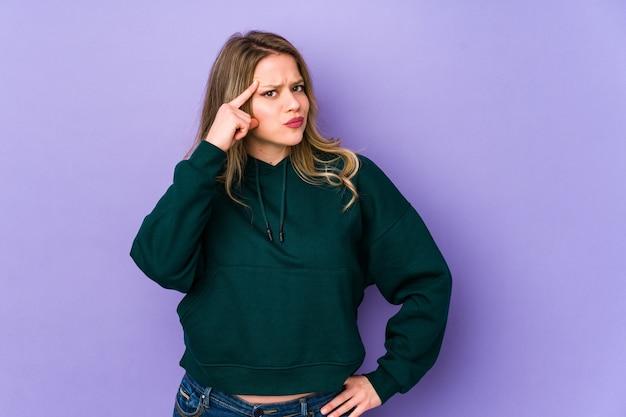 Jeune Femme Caucasienne Pointant Le Temple Avec Le Doigt, Pensant, Concentré Sur Une Tâche. Photo Premium