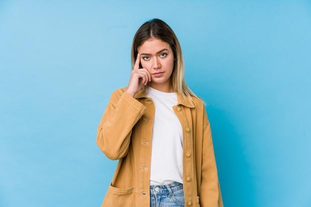 Jeune Femme Caucasienne Pointant Le Temple Avec Le Doigt, Pensant, Concentré Sur La Tâche. Photo Premium