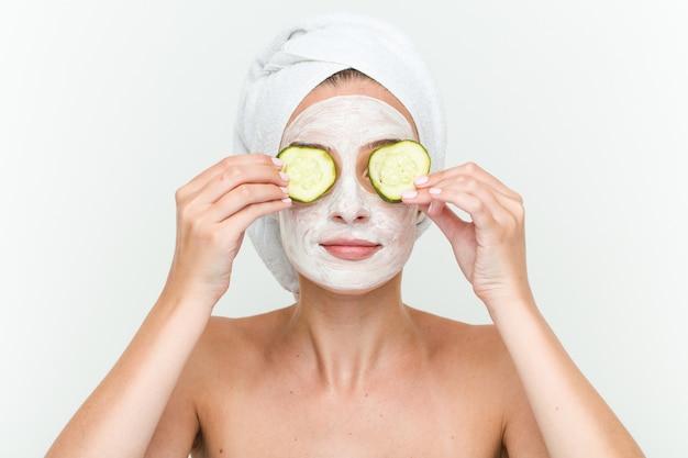 Jeune femme caucasienne, profitant d'un traitement de masque offacial avec du concombre Photo Premium