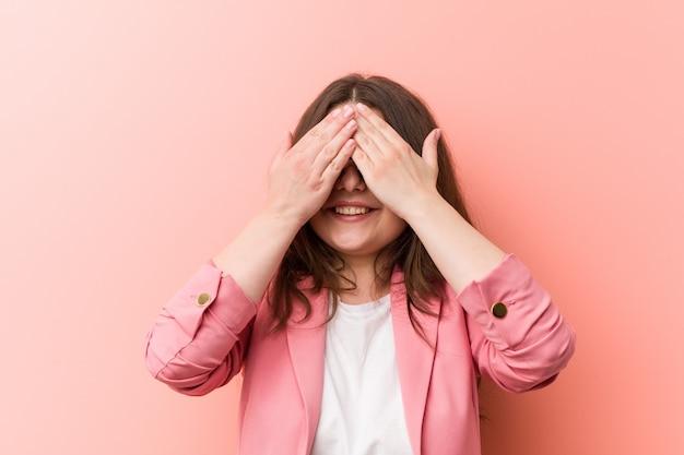 Jeune femme caucasienne de taille plus entreprise couvre les yeux avec les mains, un large sourire attend une surprise. Photo Premium