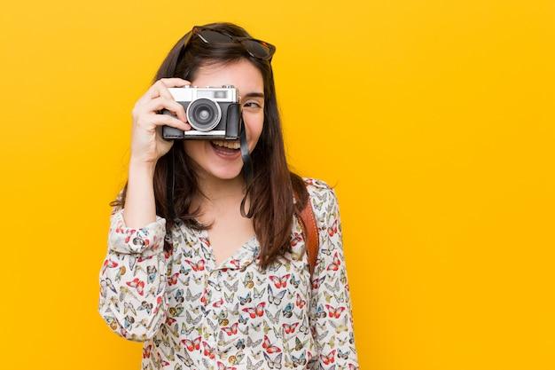 Jeune femme caucasienne tenant un appareil photo vintage Photo Premium
