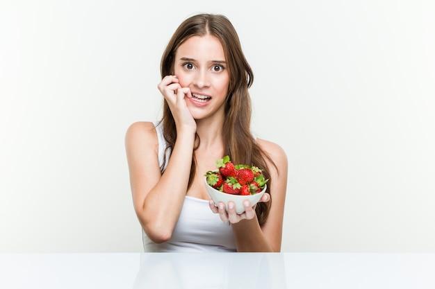 Jeune femme caucasienne tenant un bol de fraises se ronger les ongles, nerveuse et très inquiète. Photo Premium