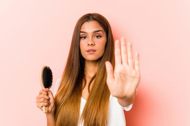 Jeune Femme Caucasienne Tenant Une Brosse à Cheveux Debout Avec La Main Tendue Montrant Le Panneau D'arrêt, Vous Empêchant. Photo Premium