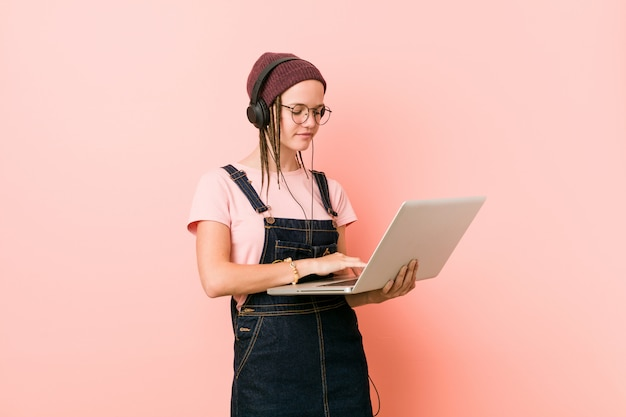Jeune Femme Caucasienne Tenant Un Ordinateur Portable Souriant Confiant Avec Les Bras Croisés. Photo Premium