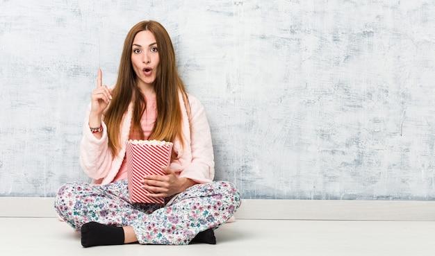 Jeune femme caucasienne tenant un seau de pop-corn ayant une très bonne idée, concept de créativité. Photo Premium