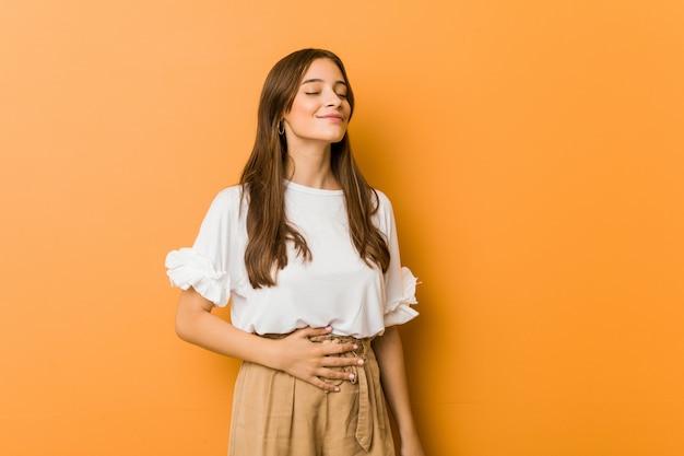 Jeune femme caucasienne touche le ventre, sourit doucement, mange et satisfaction. Photo Premium