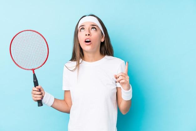 Jeune Femme Caucasique Jouant Au Badminton Isolé Pointant Vers Le Haut Avec La Bouche Ouverte. Photo Premium