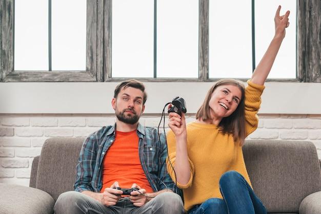 Jeune femme célébrant la victoire après avoir joué au jeu vidéo avec son mari Photo gratuit