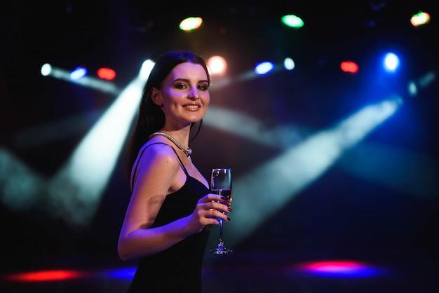 Jeune femme célèbre robe noire, tenant un verre de champagne. fête. Photo Premium