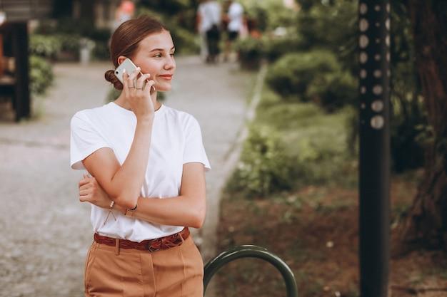 Jeune femme en centre ville parlant au téléphone Photo gratuit