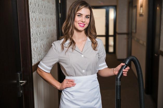 Jeune femme de chambre confiante tenant le tuyau de l'aspirateur à l'hôtel Photo gratuit