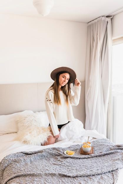 Jeune femme, chapeau, agenouillement, lit, petit déjeuner, chambre Photo gratuit