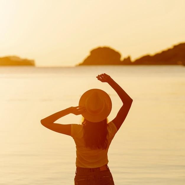 Jeune femme avec un chapeau au coucher du soleil Photo gratuit