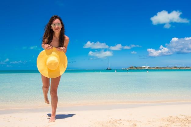 Jeune femme avec un chapeau sur la plage, profitez des vacances des caraïbes Photo Premium