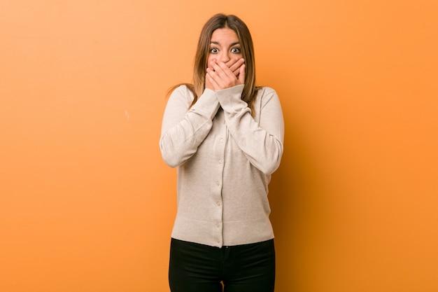 Jeune femme charismatique authentique choquée couvrant la bouche avec les mains Photo Premium