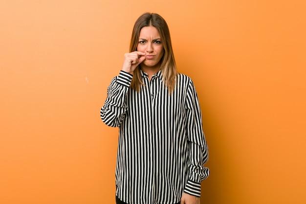 Jeune femme charismatique authentique avec les doigts sur les lèvres gardant un secret Photo Premium