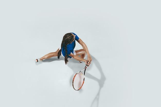 Jeune Femme En Chemise Bleue Jouant Au Tennis. Elle Frappe La Balle Avec Une Raquette. Tir Intérieur Isolé Sur Blanc. Jeunesse, Flexibilité, Puissance Et énergie. Espace Négatif. Vue De Dessus. Photo gratuit