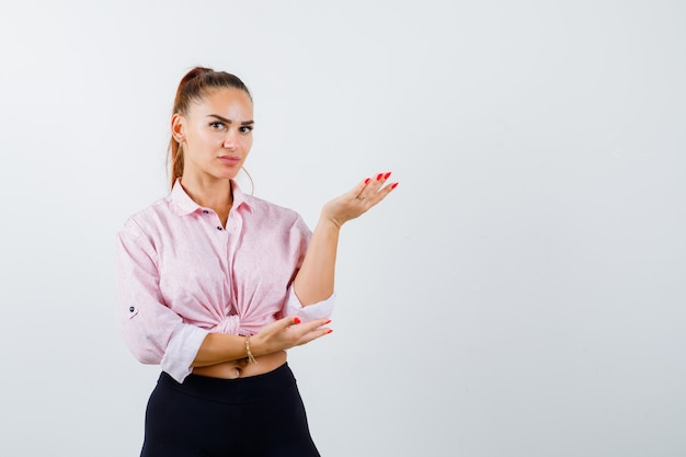 Jeune Femme En Chemise, Pantalon Levant La Main En Signe De Questionnement Et à La Perplexité, Vue De Face. Photo gratuit
