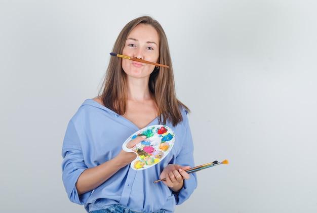 Jeune Femme En Chemise, Short Tenant Le Pinceau Et La Palette Et à La Drôle Photo gratuit