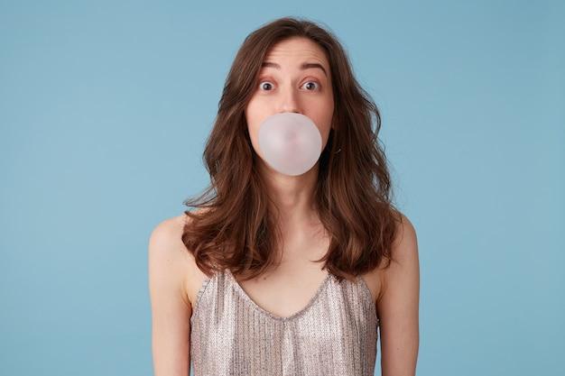 Jeune Femme En Chemisier Argenté Avec Bubblegum Photo gratuit