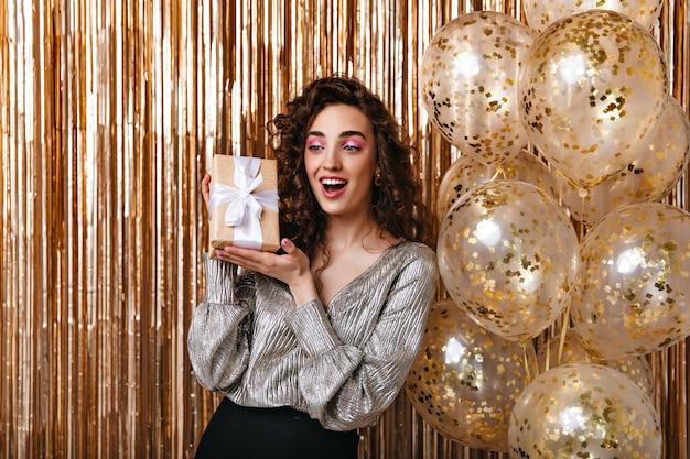 Jeune Femme En Chemisier Argenté Posant Joyeusement Avec Boîte-cadeau Photo gratuit