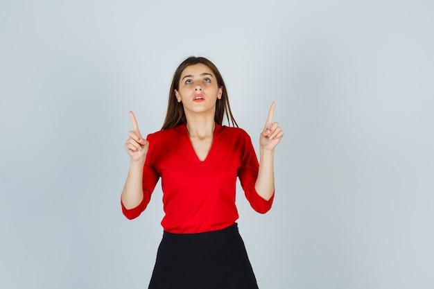 Jeune Femme En Chemisier Rouge, Jupe Noire Pointant Vers Le Haut Avec L'index Et à La Recherche Concentrée Photo gratuit