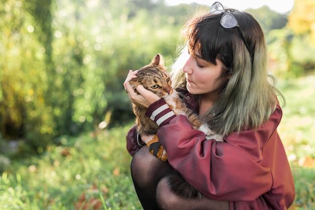 Jeune femme cherche son chat tigré dans le parc Photo gratuit