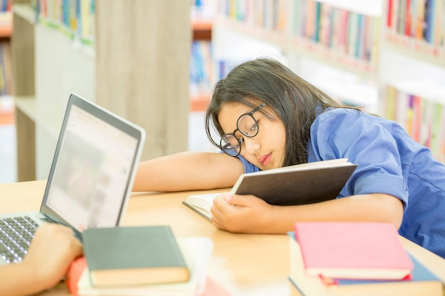 Jeune femme cheveux bruns à lunettes lire livre Photo gratuit