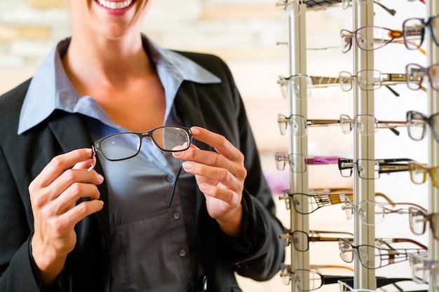 Jeune femme chez un opticien avec des lunettes, elle pourrait être client ou vendeur Photo Premium