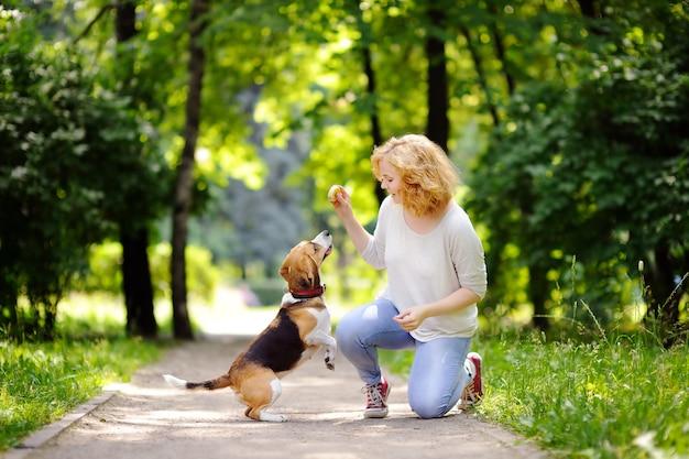 Jeune femme avec un chien beagle dans le parc de l'été. animal obéissant avec son propriétaire pratiquant la commande de saut Photo Premium