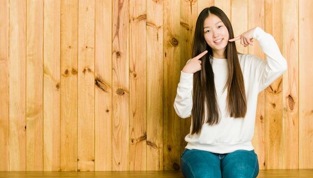 Jeune Femme Chinoise Assise Sur Une Place En Bois Sourit, Pointe Ses Doigts Vers La Bouche. Photo Premium