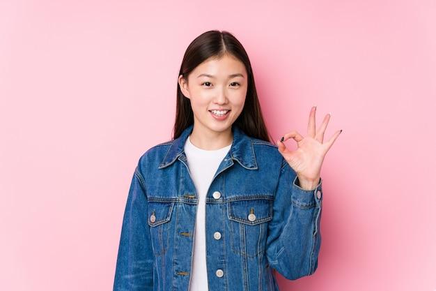 Jeune Femme Chinoise Posant Dans Un Mur Rose Isolé Gai Et Confiant Montrant Le Geste Ok. Photo Premium