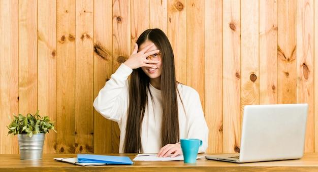 Une jeune femme chinoise qui étudie sur son bureau cligne des yeux devant la caméra, le visage embarrassé. Photo Premium