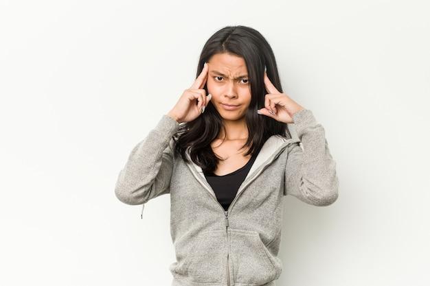 Jeune Femme Chinoise De Remise En Forme Concentrée Sur Une Tâche, Gardant Les Index Pointant La Tête. Photo Premium