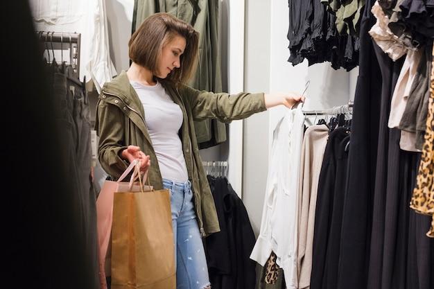 Jeune femme choisissant différentes tenues Photo gratuit