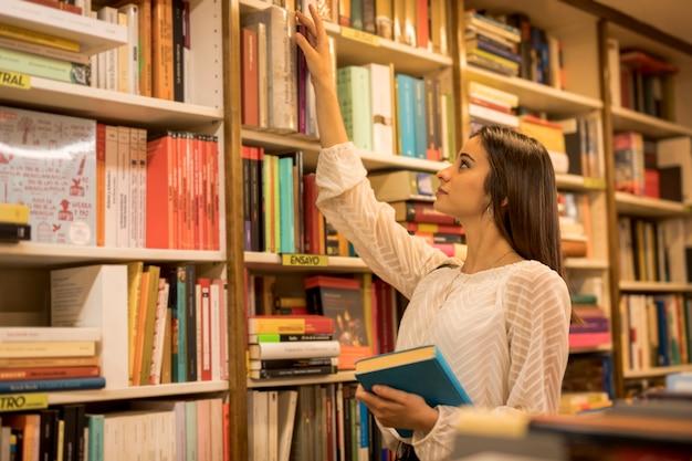 Jeune femme choisissant un livre dans la bibliothèque Photo gratuit