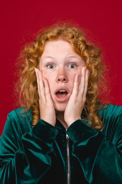 Jeune femme choquée au gingembre tenant des joues Photo gratuit