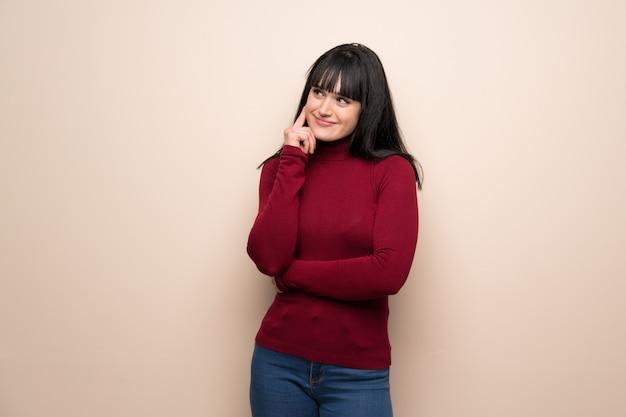 Jeune femme avec un col roulé rouge, pensant à une idée tout en levant les yeux Photo Premium