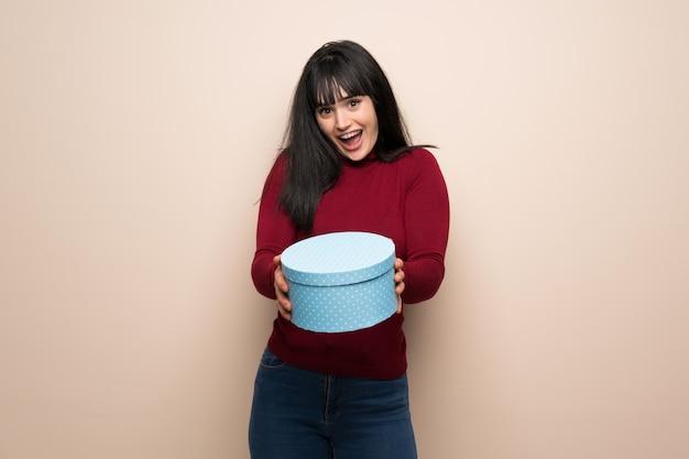 Jeune femme avec un col roulé rouge surprise parce qu'un cadeau lui a été offert Photo Premium