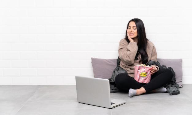 Jeune Femme Colombienne Tenant Un Bol De Pop-corn Et Montrant Un Film Dans Un Ordinateur Portable Avec Des Maux De Dents Photo Premium