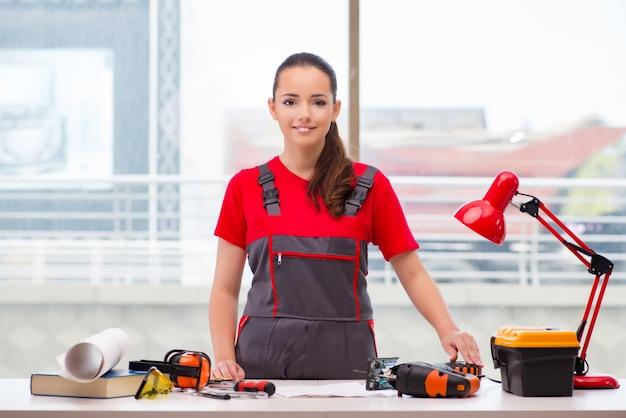 Jeune femme en combinaison faisant des réparations Photo Premium