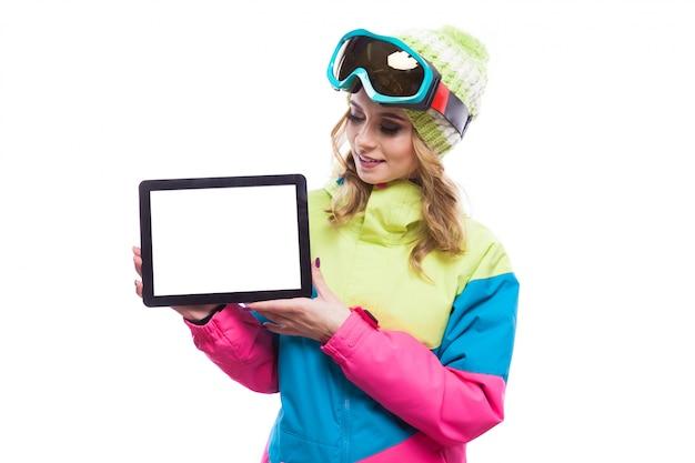Jeune femme en combinaison de ski tenir une tablette vierge Photo Premium