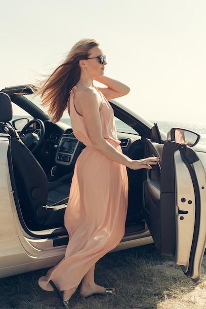 Jeune femme conduire une voiture sur la plage Photo Premium