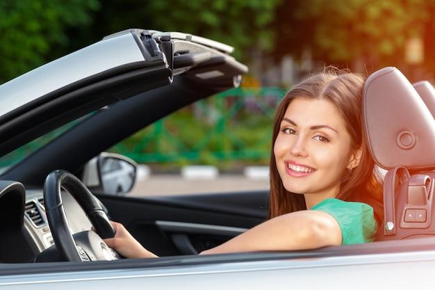 Jeune femme conduisant une voiture dans la ville. Photo Premium