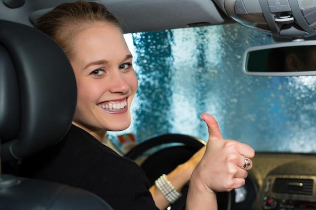 Jeune femme conduit une voiture dans une station de lavage Photo Premium