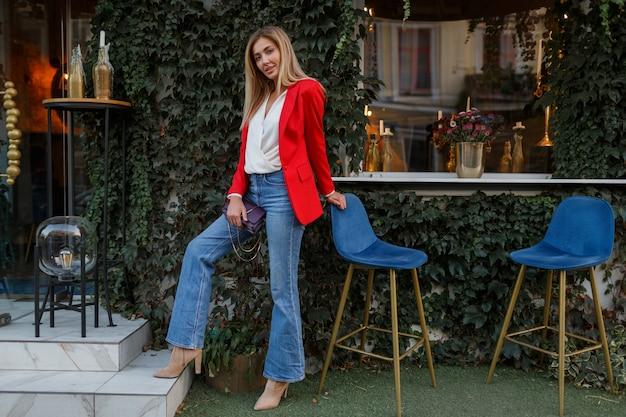 Jeune Femme Confiante Européenne Avec Un Sourire Candide Posant En Plein Air Dans Le Bar. Porter Une Veste à La Mode Rouge Photo gratuit