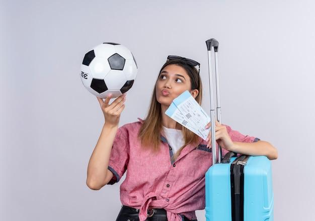 Une Jeune Femme Confiante Portant Une Chemise Rouge Et Des Lunettes De Soleil Regardant Un Ballon De Football Tout En Tenant Des Billets D'avion Et Une Valise Bleue Sur Un Mur Blanc Photo gratuit