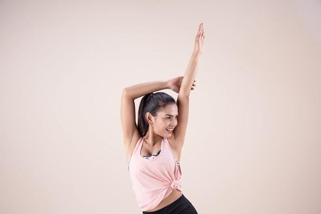 La Jeune Femme En Costume D'exercice, Levant Les Mains En L'air, Faisant Des Exercices De Danse Photo Premium