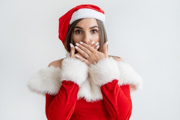 Jeune femme en costume de père noël couvrant la bouche avec surprise Photo gratuit