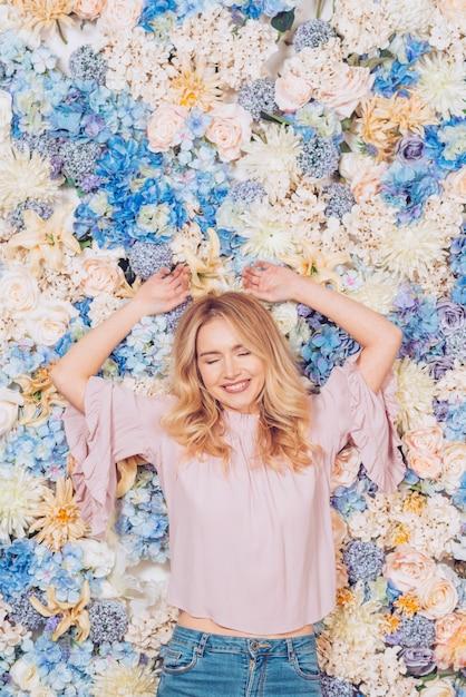 Jeune femme couchée sur des fleurs aux couleurs vives Photo gratuit